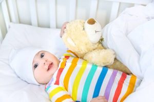 bébé est couché avec nounours dans son berceau blanc