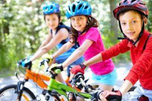 Trois enfnats sur leur vélos nous regarde