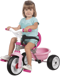petite fille assise sur tricycle rose