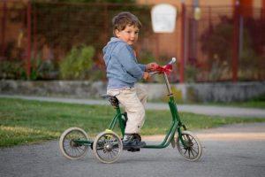 Enfant assis sur tricycle usé