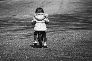 petite fille assise sur une draisienne
