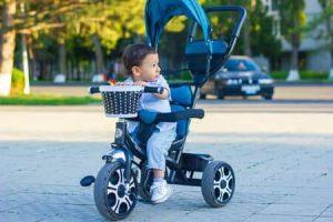Petit garçon sur tricycle bleu regarde au loin