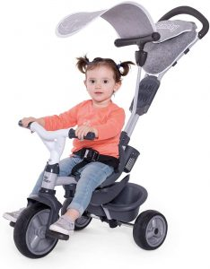 petite fille assise sur le tricycle évolutif blanc et gris