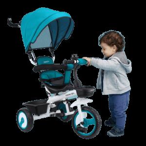 petit garçon tient le guidon du tricycle bleu