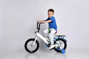 garçon avec vélo à roues stabilisatrices