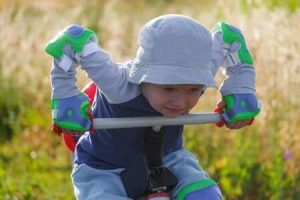 bébé avec chapeau gris s'appuie sur le guidon