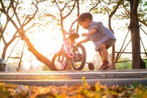 petit garçon touche le vélo à roulettes de sa main droite