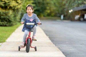 petite fille asiatique se promène sur son vélo à roulettes