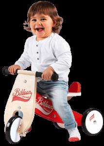petit garçon assis sur un tricycle en bois