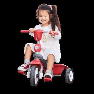 petite fille assise sur un tricycle rouge