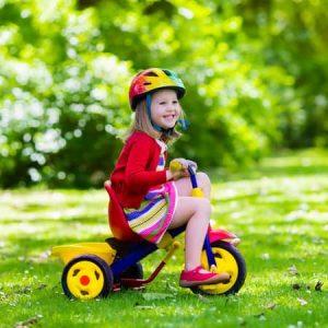 fille asssise sur un tricycle à roues jeunes