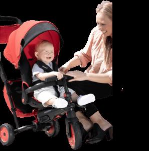 maman rigole avec son bébé assis sur un tricycle rouge