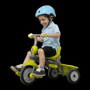 petit garçon avec casque bleu pédale sur un tricycle vert