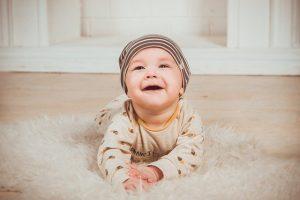 bébé qui rigole allongé sur le sol