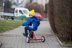 enfant avec un manteau bleu est assis sur un tricycle et pédale dans la rue