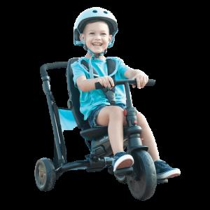 l'enfant est assis sur un tricycle et porte un casque bleu