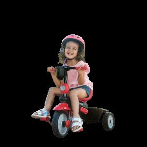 petite fille avec un casque rose fait du tricycle
