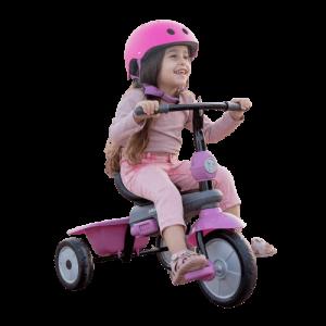 petite fille porte un casque rose et est vassie sur un tricycle avec un garde boue et une benne arrière rose