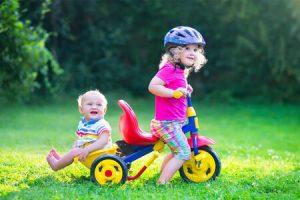 petite fille transpoorte un petit garçon sur le tricycle