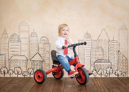 petit garçon assis sur tricycle rouge