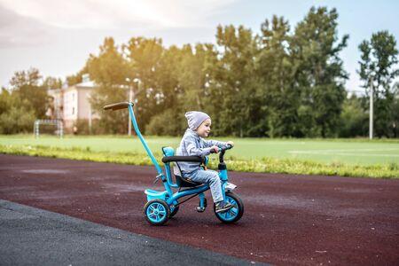 bébé est assis sur un tricycle bleu. Il attend qu'on le pousse