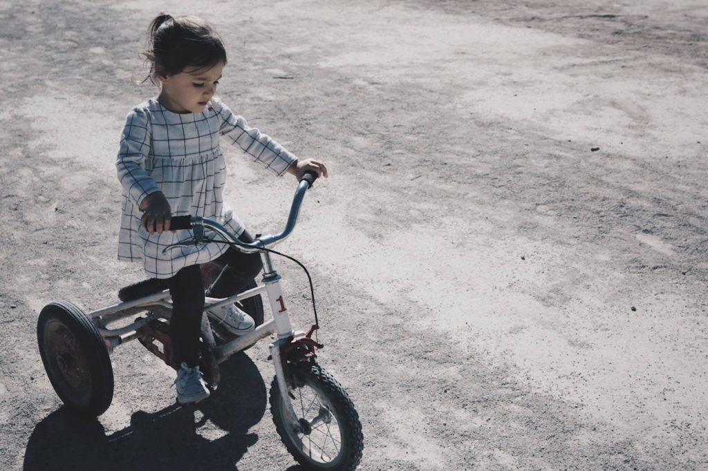 garande fille pédale sur un tricycle