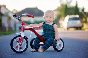 Un bébé est assis sur un tricycle rouge très allongé