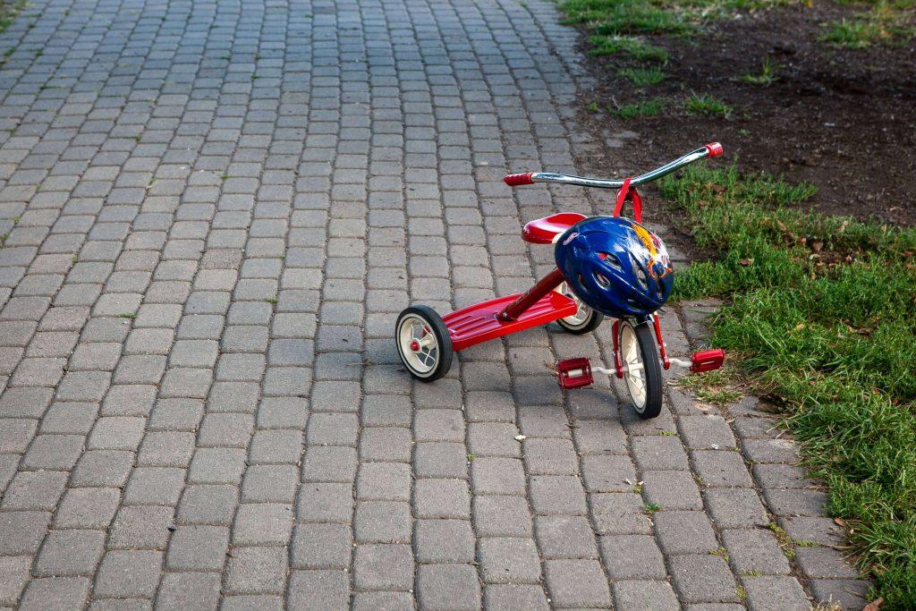 tricycle rouge avec un casque bleu posé sur le guidon