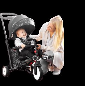 bébé et maman rigolent autour d'un tricycle noir