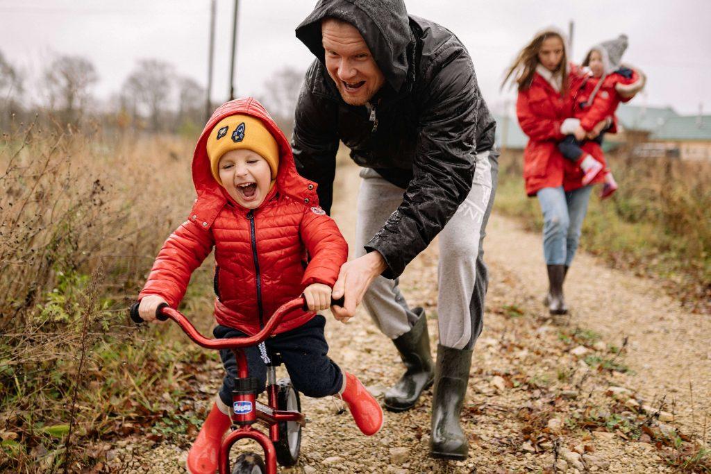 petit garçon rigole sur sa draisienne sur un chemin